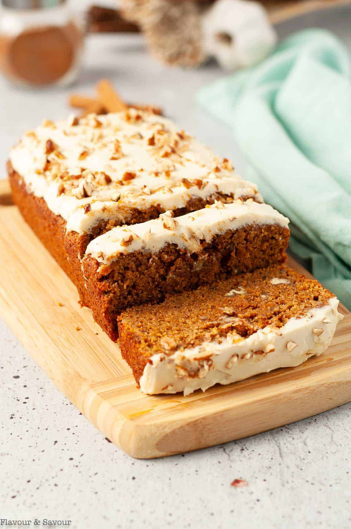 slices of pumpkin bread with cream cheese frosting on a board