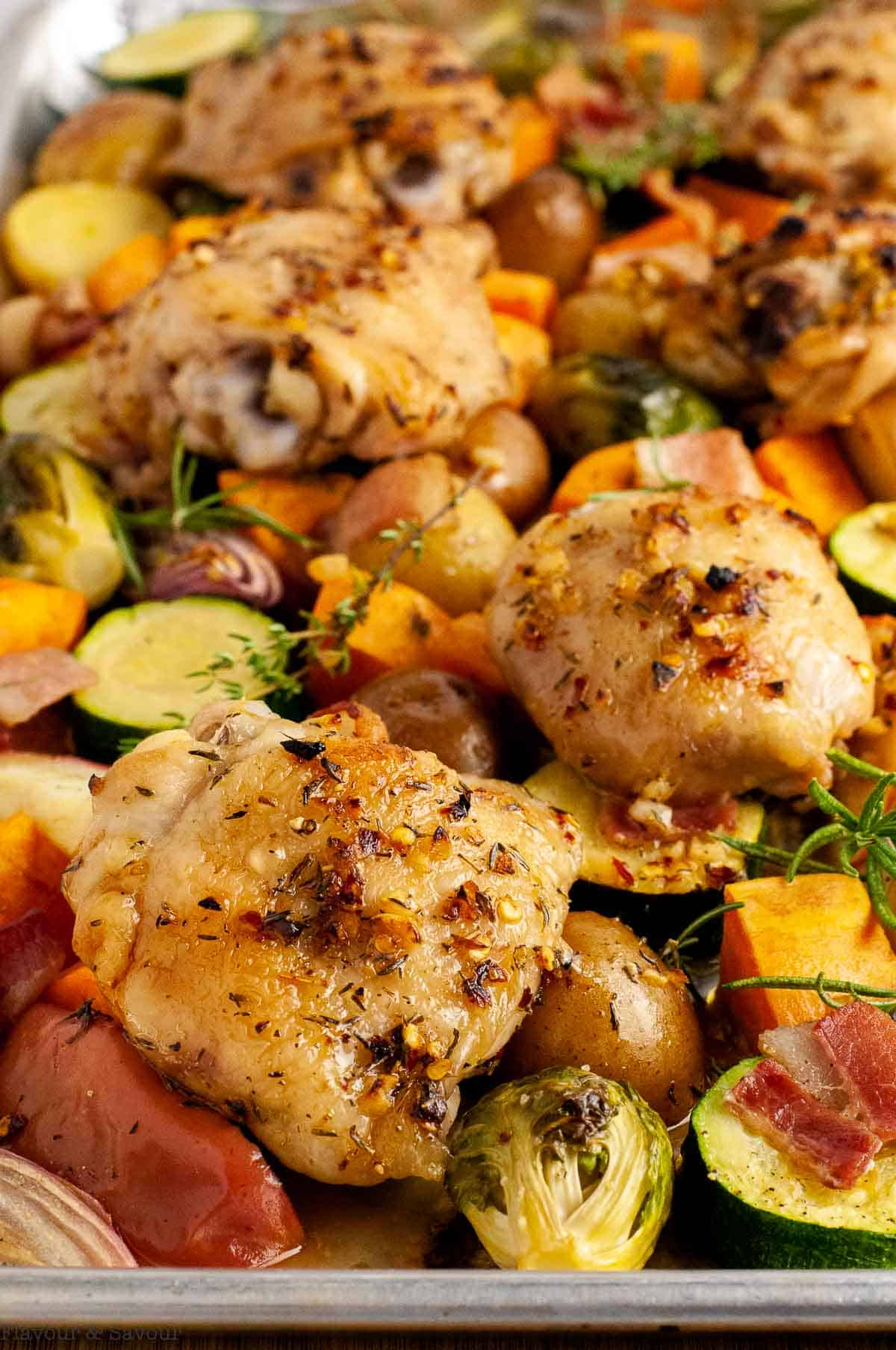 a sheet pan loaded with roasted chicken thighs, harvest vegetables, bacon and apples