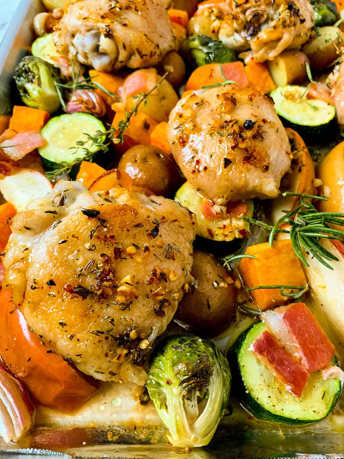 Roasted chicken thighs and fall vegetables on a sheet pan
