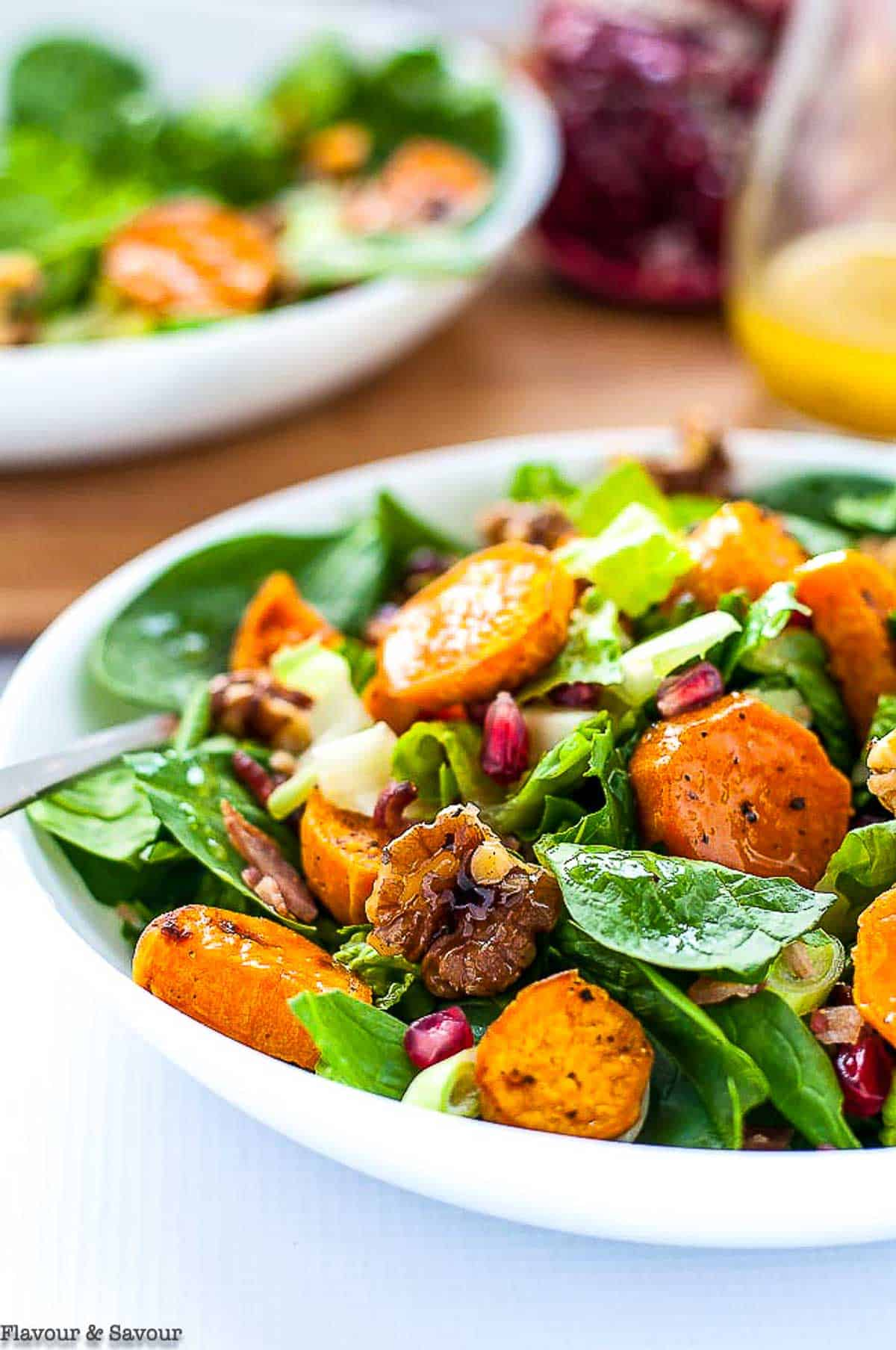 a bowl of spinach salad with roasted sweet potatoes, walnuts and pomegranate.