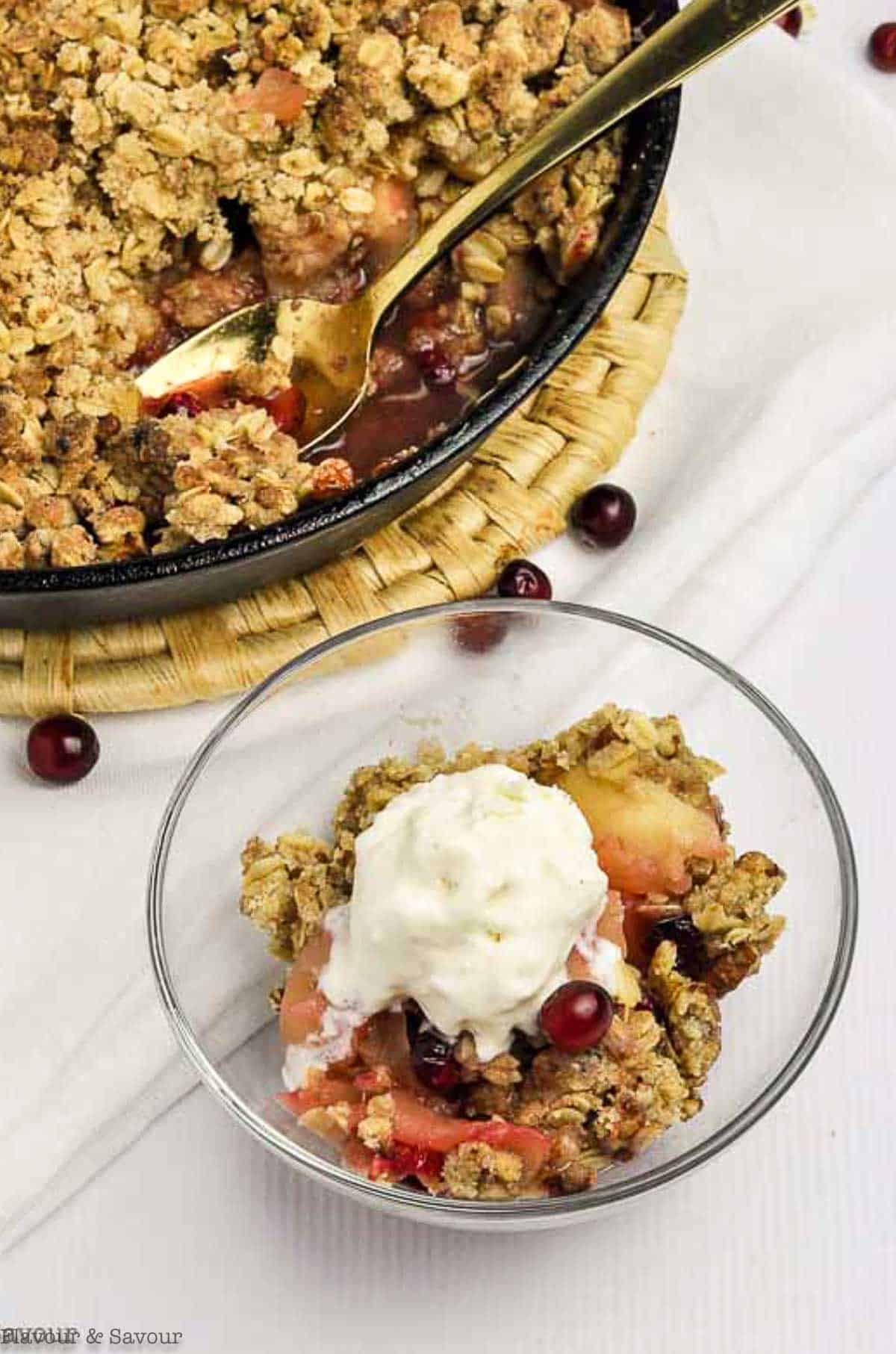 Skillet Cranberry Apple Crisp in a bowl beside a cast iron pan